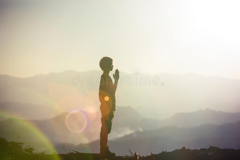 Faith of christian concept: Spiritual prayer hands. Over sun shine with blurred beautiful sunset background stock photography