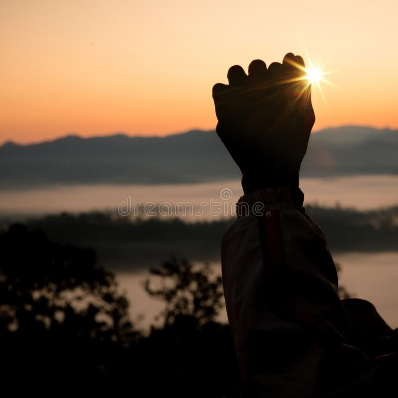 Faith of christian concept: Spiritual prayer hands over sun shine. With blurred beautiful sunset background royalty free stock images