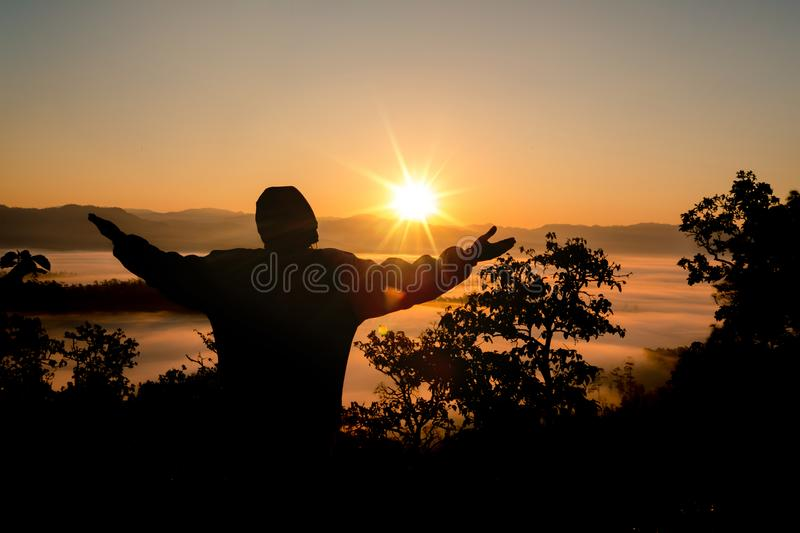 Faith of christian concept: Spiritual prayer hands over sun shine. With blurred beautiful sunset background stock image