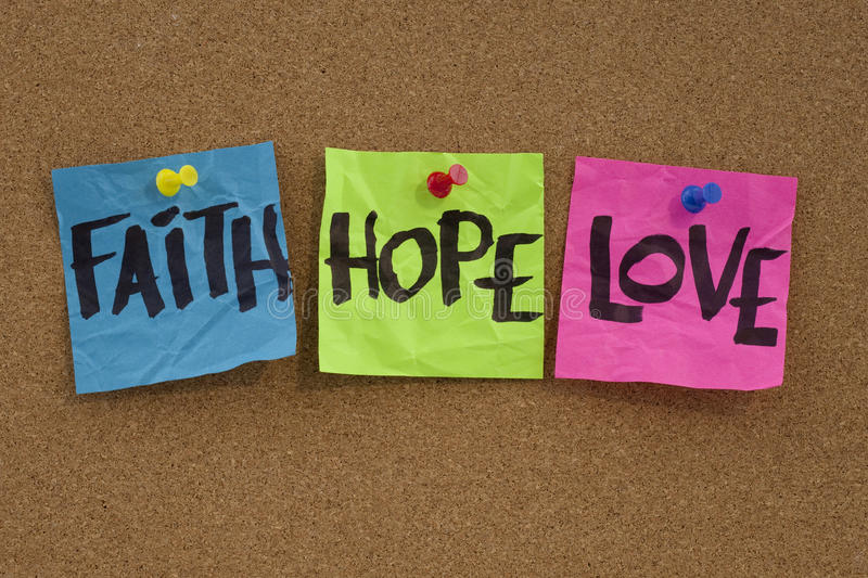 Faith, hope and love. Spiritual reminder or metaphysical concept - faith, hope and love handwritten on colorful notes and posted on cork bulletin board stock photo