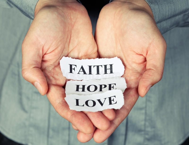 Faith, Hope and Love. Torn pieces of paper with the words Faith, Hope and Love in the woman's palms stock photos