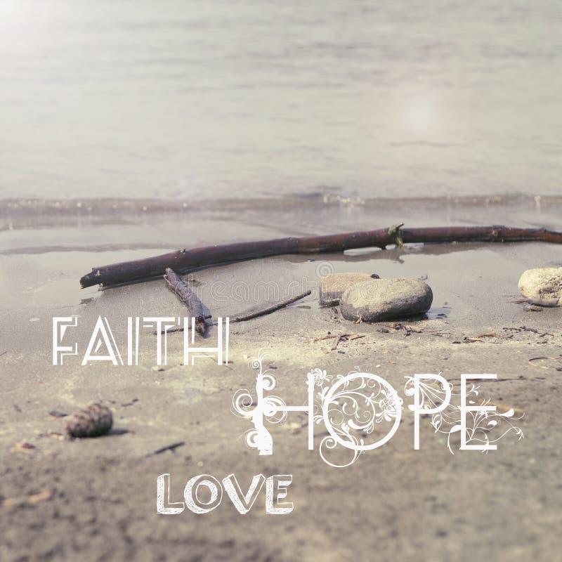 Faith Hope Love. Words on sand stock photos