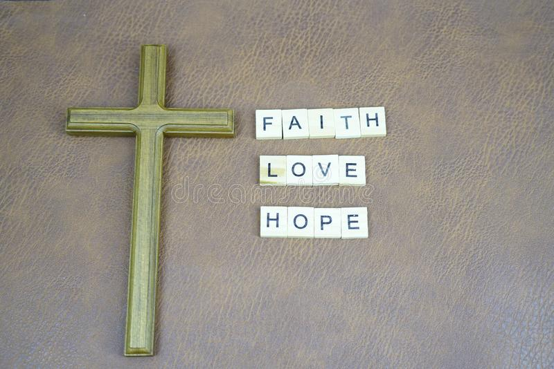 Faith love hope letters and holy cross on the leather table stock photos