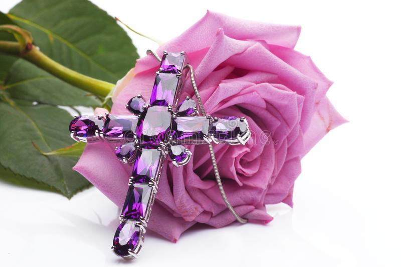Faith - A purple rose with a necklace. A beautiful necklace with amethyst and a purple rose in white background. Amethyst is a semiprecious stone often used in stock images