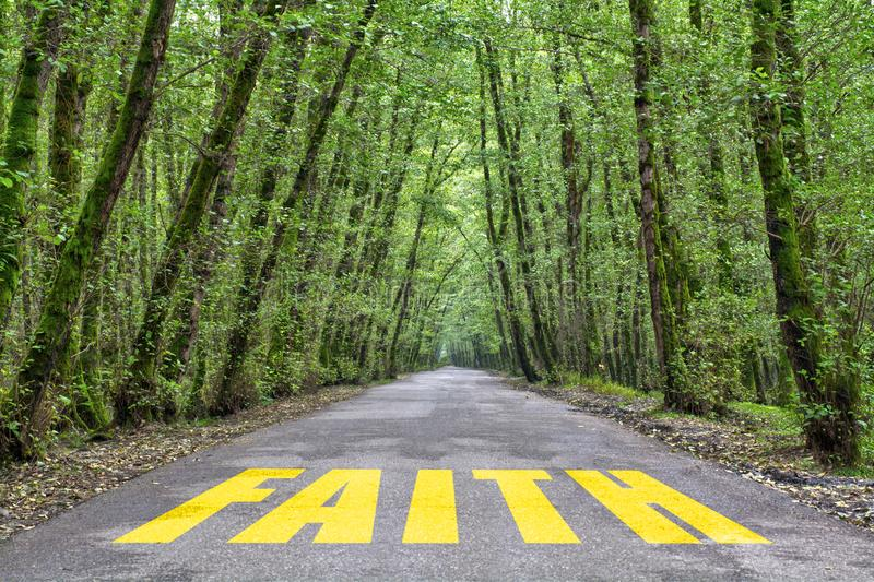 Jungle road to faith. Faith word written on jungle road with tall tree two side, green road stock photography