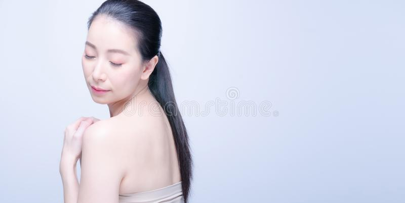 Faithful asian woman closes eyes and hands on chest near heart, shows her kindness or favour, expresses sincere emotions, being stock photo