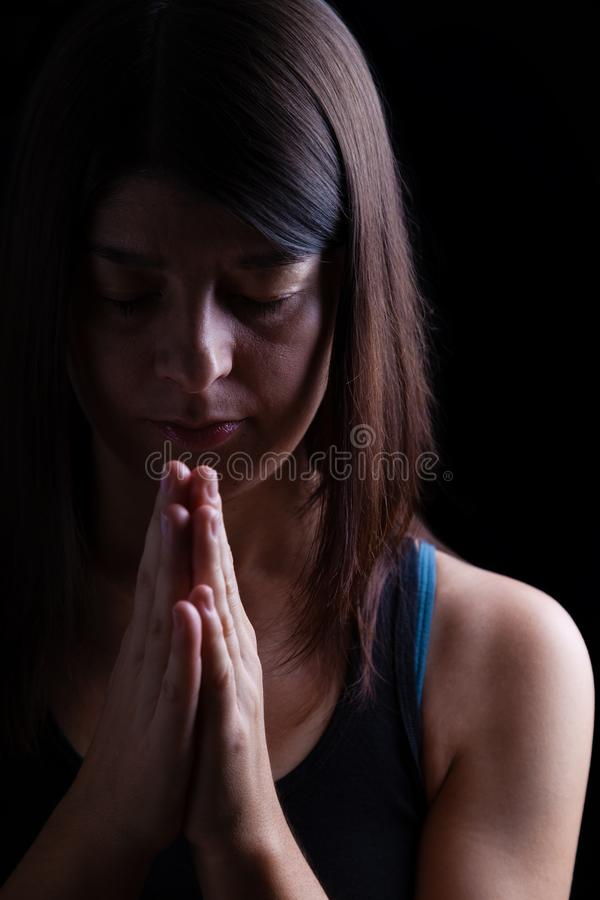 Faithful athletic woman praying, with hands folded in worship to god royalty free stock photography