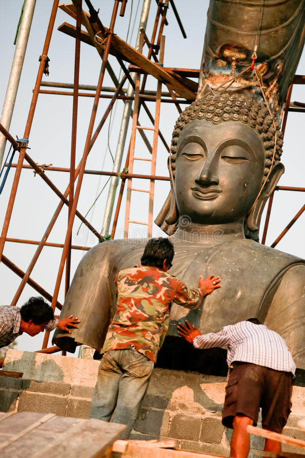 Faithful dedication. Devout Buddhists dedicate time to renovate a Buddha statue that was damaged by flood waters stock photos