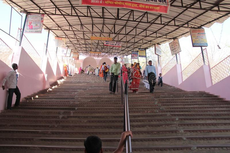 Faithful Devotees climb steep steps to temple on pilgrimage in India stock photo