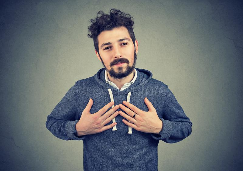 Faithful man keeps hands on chest near heart, shows kindness expresses sincere emotions royalty free stock photos