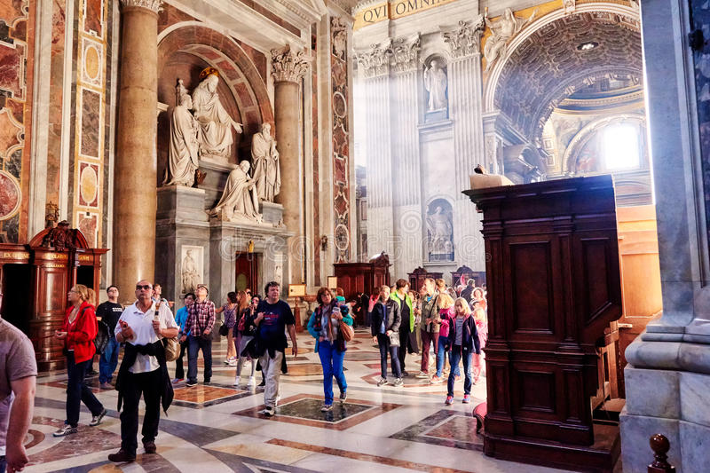 Faithful and tourists take a tour of the interior of the basilica of St. Peter's in the Vatican, Rome, Italy stock image