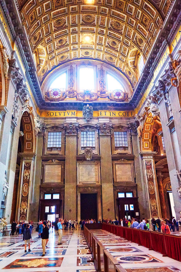Faithful and tourists take a tour of the interior of the basilica of St. Peter's in the Vatican, Rome, Italy. VATICAN CITY, VATICAN - OCTOBER 29: The faithful stock photo