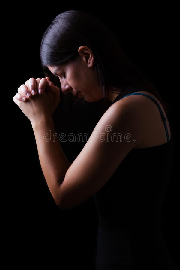 Faithful woman praying, hands folded in worship to god with head down and eyes closed stock photo