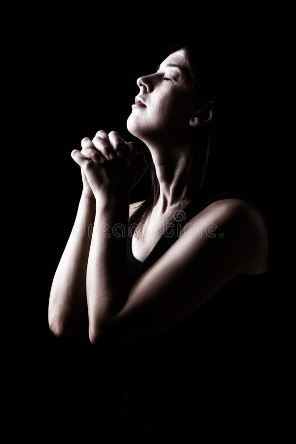 Faithful woman praying, hands folded in worship to god with head up and closed eyes royalty free stock photo