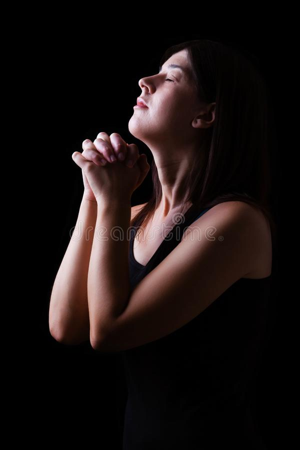 Faithful woman praying, hands folded in worship to god with head up and closed eyes stock image