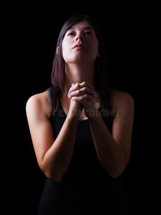 Faithful woman praying, hands folded in worship to god with looking up royalty free stock images