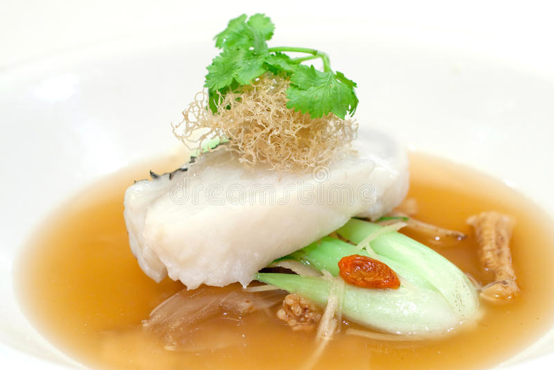 Faixa cozinhada do bacalhau em uma cama dos vegetais imagens de stock royalty free