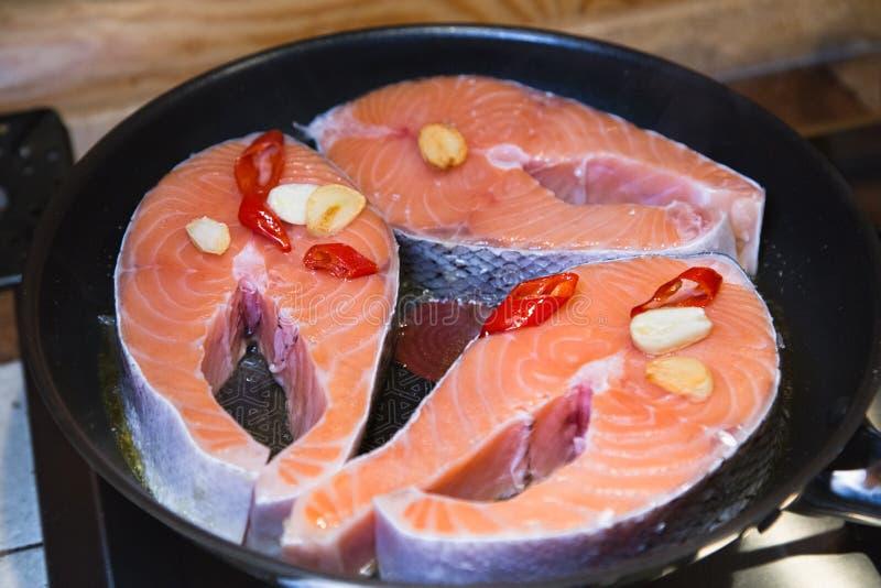 Faixa crua dos salmões na frigideira Bifes de salmões com alho e pimenta vermelha foto de stock
