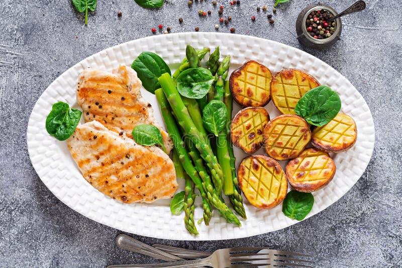 A faixa da galinha cozinhou em uma grade com uma decoração do aspargo e cozeu batatas imagem de stock royalty free