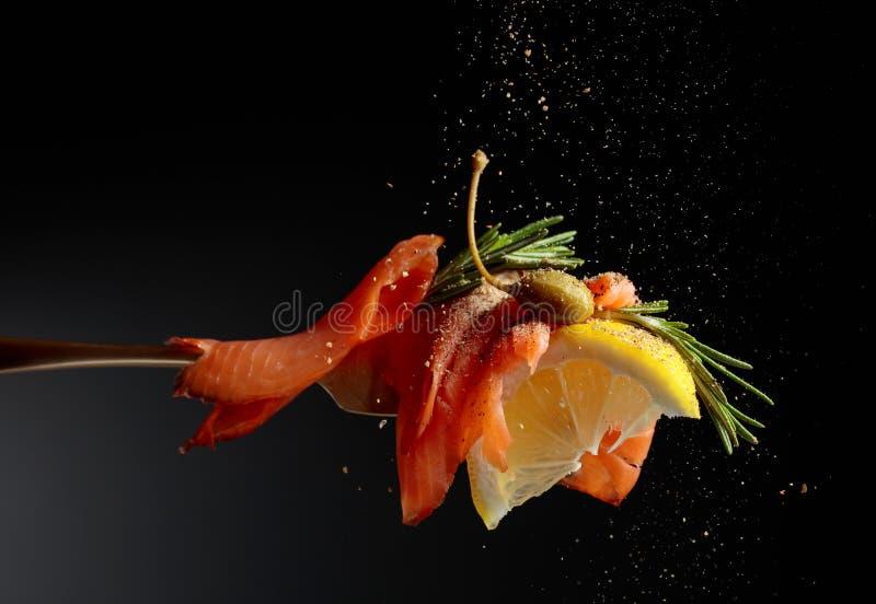 A faixa da truta, a fatia do lim?o, as alcaparras e os alecrins polvilham com a pimenta foto de stock