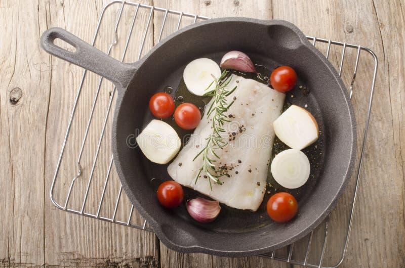 Faixa de bacalhau em uma bandeja do ferro fundido fotografia de stock royalty free
