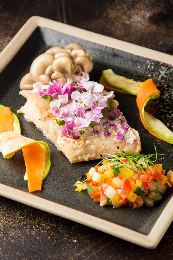 Faixa de peixes brancos fritada com as flores, os cogumelos e os vegetais tartare Servi?o bonito do restaurante, alimento elegant fotos de stock