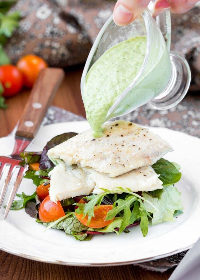Faixa de peixes brancos fritada com salada dos tomates, rúcula, ervas fotos de stock