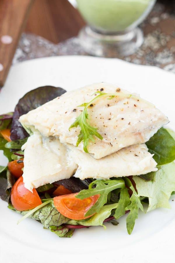 Faixa de peixes brancos fritada com salada dos tomates, rúcula, ervas foto de stock