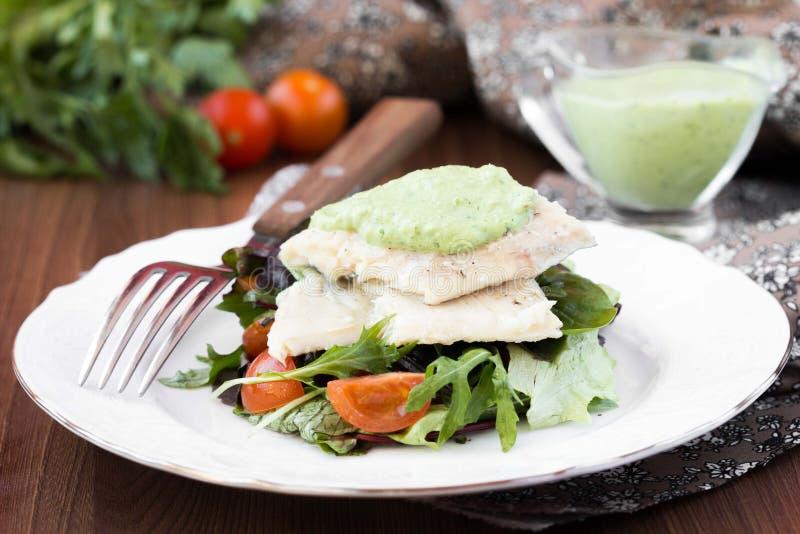Faixa de peixes brancos fritada com salada dos tomates, rúcula, ervas imagem de stock