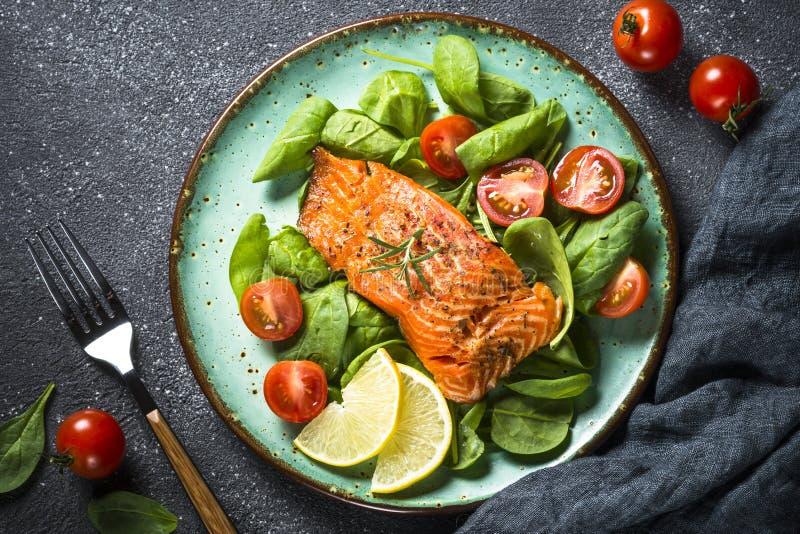 Faixa de peixes cozida dos salmões com opinião superior da salada fresca imagens de stock