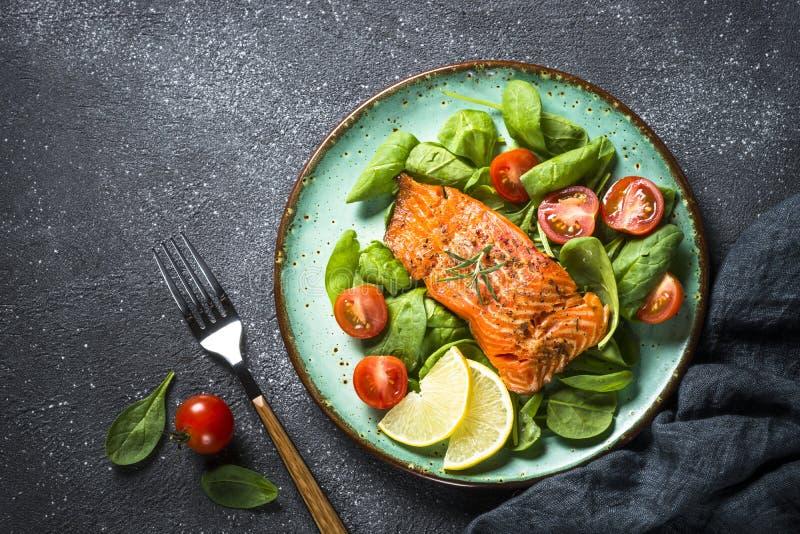 Faixa de peixes cozida dos salmões com opinião superior da salada fresca fotografia de stock royalty free