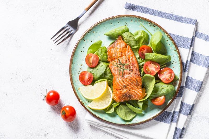 Faixa de peixes cozida dos salmões com opinião superior da salada fresca no branco fotos de stock