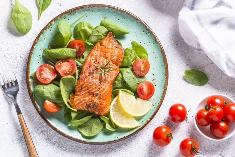 Faixa de peixes cozida dos salmões com opinião superior da salada fresca no branco imagens de stock