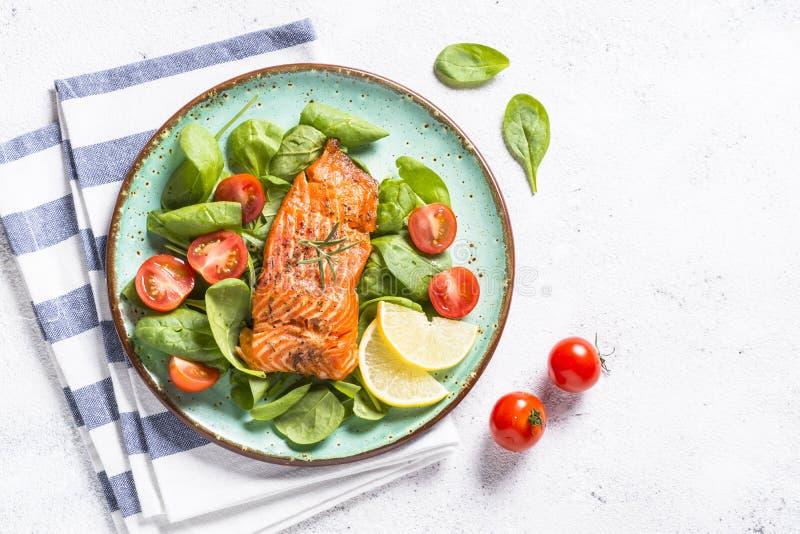 Faixa de peixes cozida dos salmões com opinião superior da salada fresca no branco foto de stock royalty free