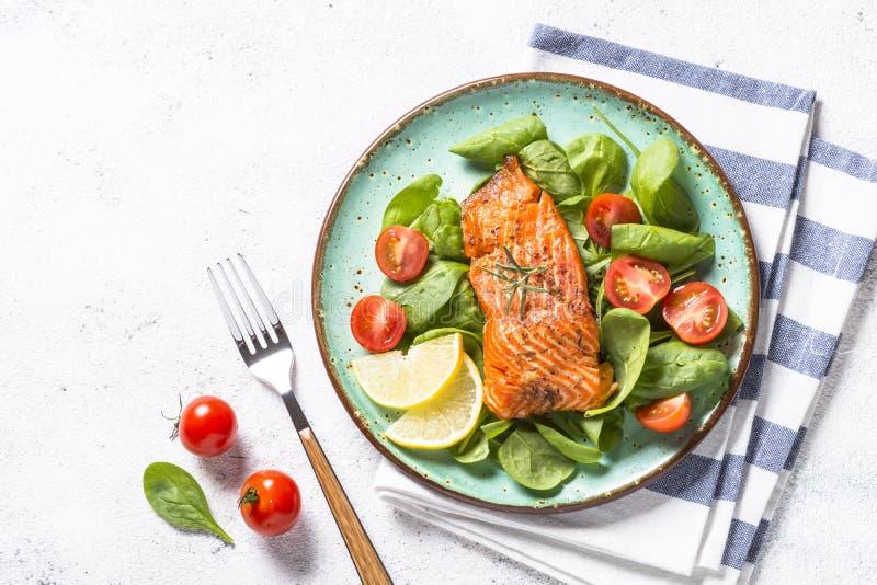 Faixa de peixes cozida dos salmões com opinião superior da salada fresca no branco fotografia de stock