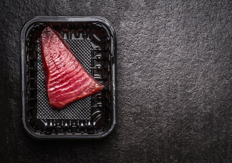 Faixa de peixes crua do atum na caixa plástica foto de stock