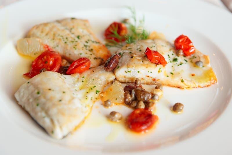 Faixa de peixes fritada com alcaparras e tomates foto de stock royalty free