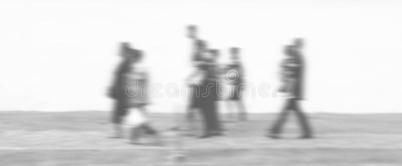 Faixa de travessia com alguns povos que cruzam a estrada no primeiro plano e algum fundo em uma estrada molhada fotos de stock royalty free