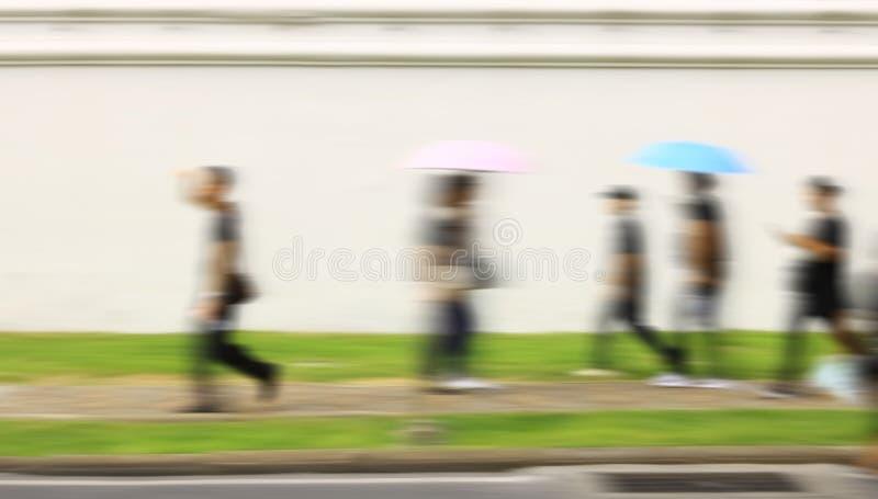 Faixa de travessia com alguns povos que cruzam a estrada no primeiro plano e algum fundo em uma estrada molhada imagem de stock