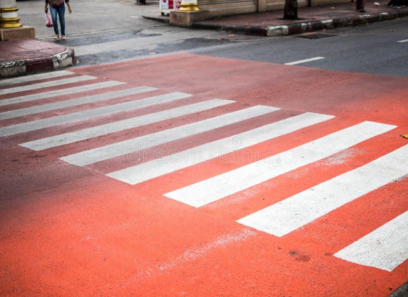 Faixa de travessia na estrada, cruzamento pedestre do ‹de Red†com as listras vermelhas e brancas sem povos perto acima O concei fotografia de stock