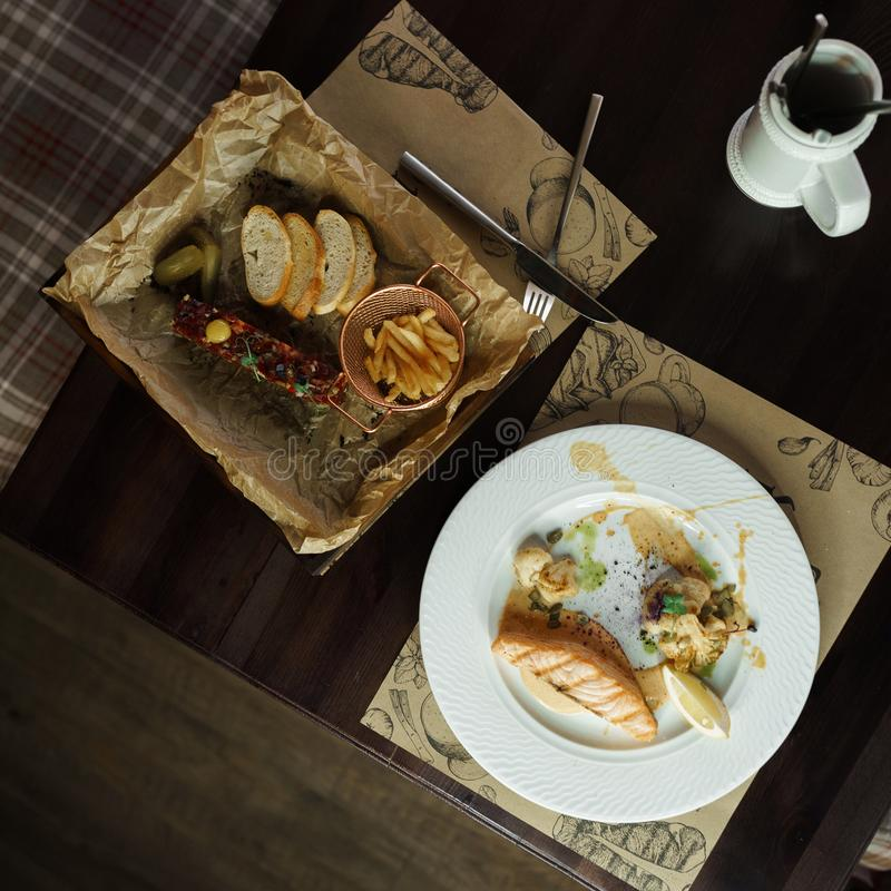 Faixa deliciosa dos salmões com as sementes de abóbora com a couve-flor no molho Tártaro apetitoso da carne com pepino conservado foto de stock royalty free