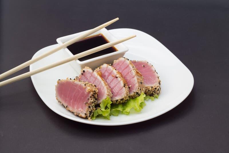 Faixa do atum no prato branco com molho da salada e de soja foto de stock royalty free
