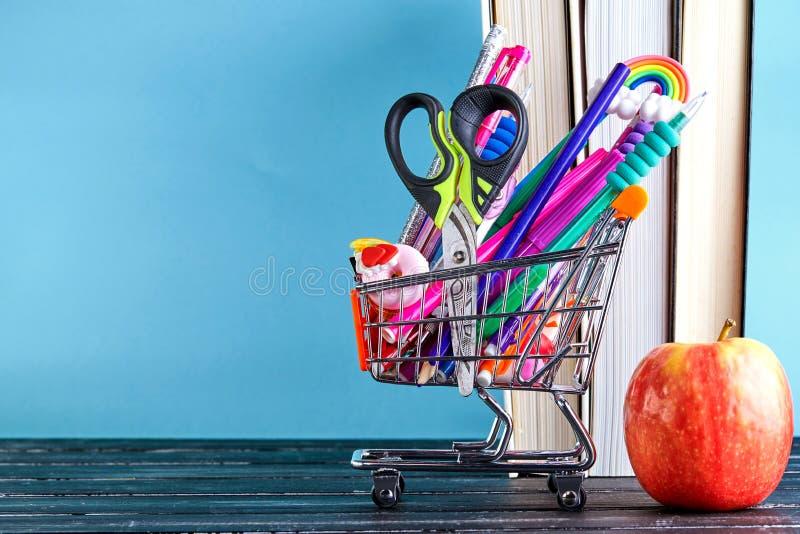 Faixa do carrinho de compras com material escolar em fundo azul com livros e uma maçã com espaço em cópia. De volta à escola imagem de stock royalty free