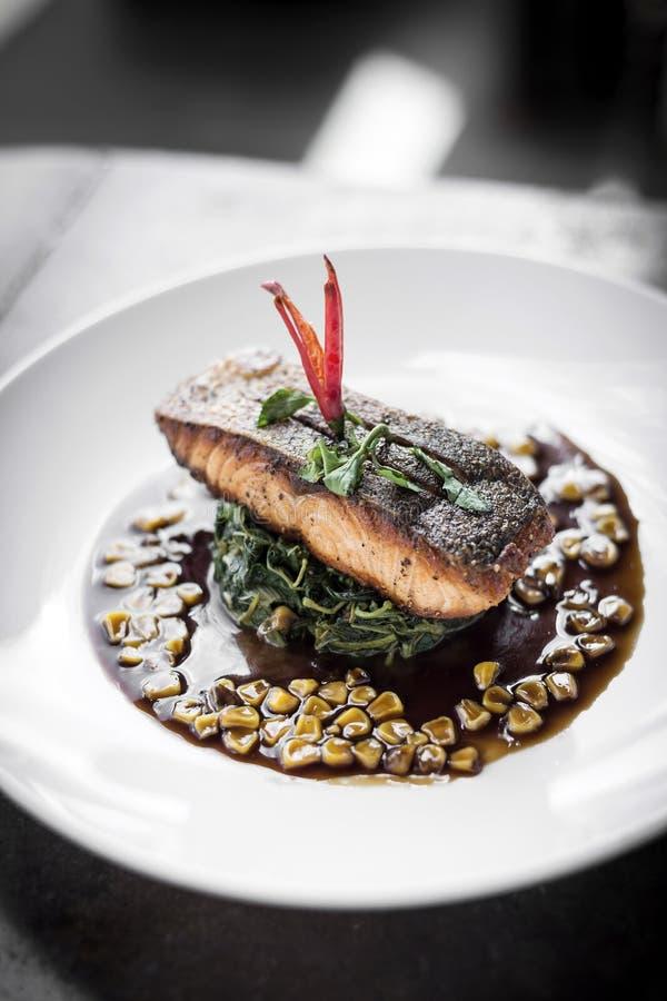 Faixa dos salmões com espinafres e milho cozinhados com molho doce da soja e da ostra foto de stock royalty free