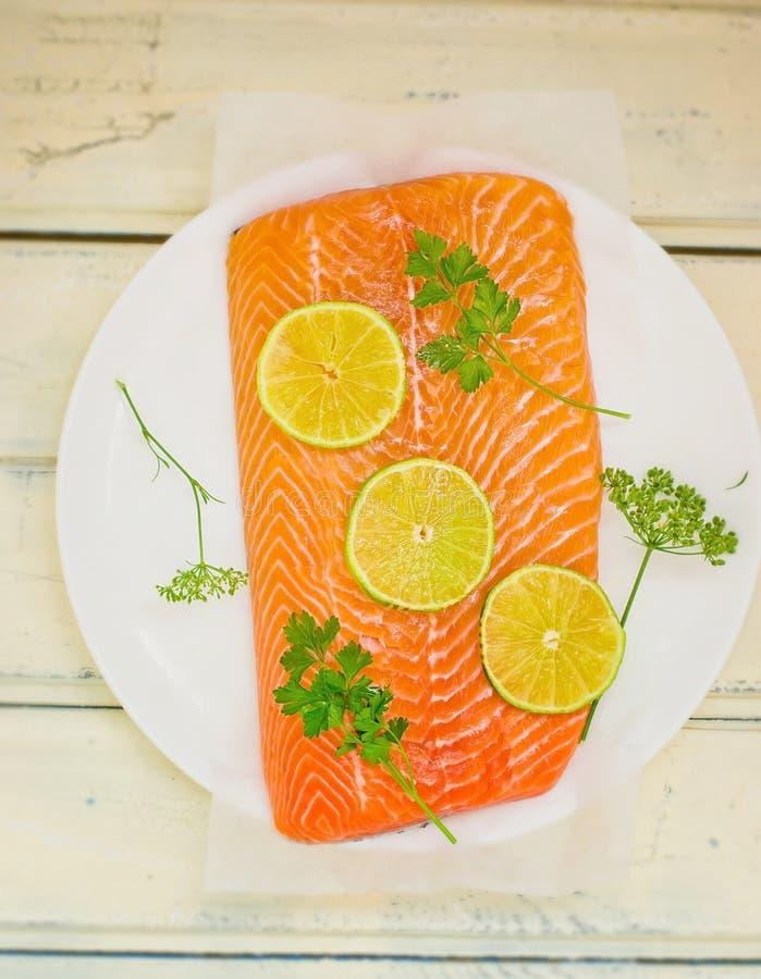 Faixa fresca, bruta de um salmão com fatias de um cal e verdes imagens de stock