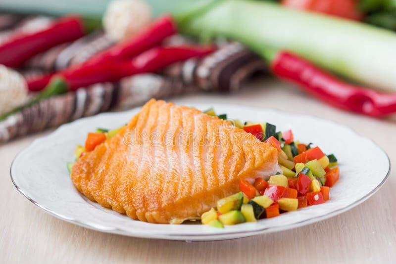 Faixa fritada de salmões vermelhos dos peixes com vegetais roasted imagem de stock royalty free