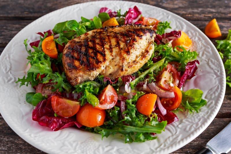 Faixa grelhada do peito de frango com salada fresca dos vegetais dos tomates Alimento saudável do conceito imagens de stock
