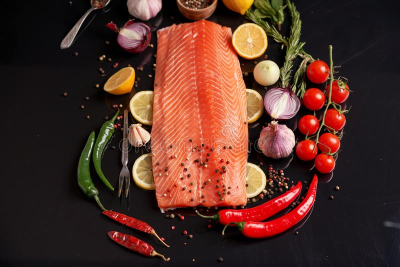 Faixa inteira dos salm?es em um fundo reflexivo escuro com pimenta colorida ?s bolinhas, alho, lim?o, alecrim, cebola, tomates de fotografia de stock