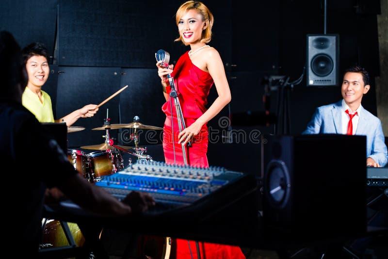 Faixa profissional asiática na mistura do estúdio de gravação foto de stock royalty free
