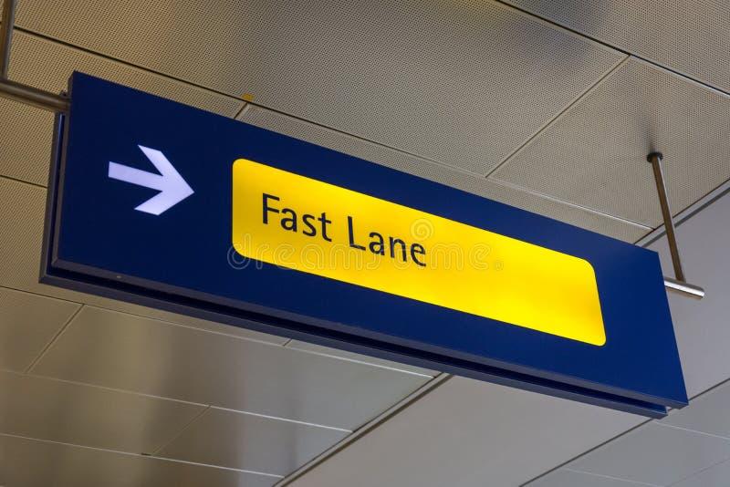 A faixa rápida assina dentro azul e amarelo no aeroporto fotos de stock